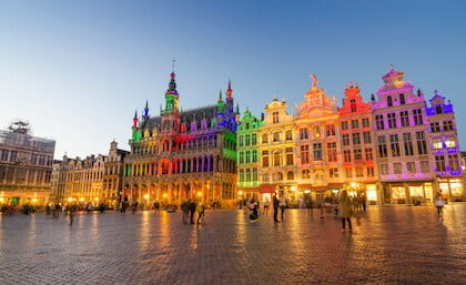 Grand Place con iluminación colorida al atardecer en Bruselas.